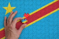 Democratic Republic of the Congo flag is depicted on a puzzle, which the man`s hand completes to fold.  vector illustration