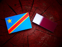Democratic Republic of the Congo flag with Qatari flag on a tree stump isolated. Democratic Republic of the Congo flag with Qatari flag on a tree stump Stock Photo