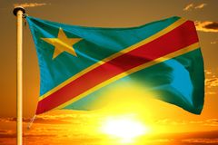 Democratic Republic of Congo flag weaving on the beautiful orange sunset with clouds background. Democratic Republic of Congo flag weaving on the beautiful stock image