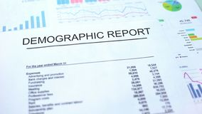 Demographic report lying on table, graphs charts and diagrams, official document