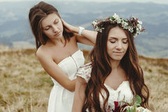 Demoiselle d'honneur élégante aidant la jeune mariée magnifique préparant, weddin de boho Photo stock