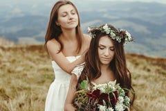 Demoiselle d'honneur élégante aidant la jeune mariée magnifique préparant, weddin de boho Images libres de droits