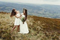 Demoiselle d'honneur élégante aidant la jeune mariée magnifique préparant, weddin de boho Photos libres de droits