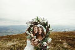 Demoiselle d'honneur élégante et jeune mariée magnifique riant et regardant le throu Images libres de droits