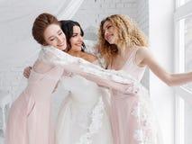 Demoiselle d'honneur étreignant la jeune mariée dans la chambre à coucher blanche pendant le matin Amitié de femmes Photographie stock libre de droits
