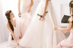 Demoiselle d'honneur agréable regardant la jeune mariée et l'aidant Photos libres de droits