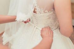 Demoiselle d'honneur attachant l'arc sur la robe de mariage Image libre de droits