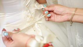 Demoiselle d'honneur attachant l'arc sur la robe de mariage banque de vidéos