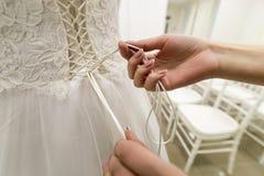 Demoiselle d'honneur attachant le noeud au dos de la robe de mariage de jeunes mariées Photos stock