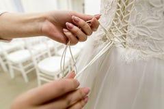 Demoiselle d'honneur attachant le noeud au dos de la robe de mariage de jeunes mariées fin Photos stock