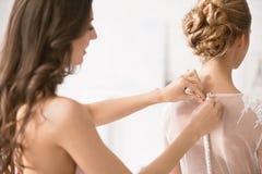 Demoiselle d'honneur avec du charme aidant la jeune mariée avec sa robe Photographie stock