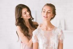 Demoiselle d'honneur avec plaisir aidant la jeune mariée avec sa robe Photos libres de droits