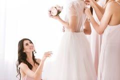 Demoiselle d'honneur avec plaisir regardant la jeune mariée Photographie stock libre de droits