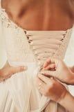 Demoiselle d'honneur boutonnant la robe sur la jeune mariée Photos stock