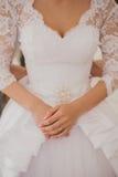 Demoiselle d'honneur boutonnant la robe sur la jeune mariée Photo libre de droits