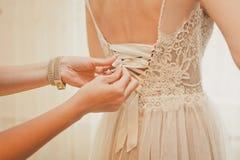 Demoiselle d'honneur boutonnant la robe sur la jeune mariée Photo stock