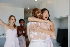 Demoiselle d'honneur félicitant la jeune mariée avant cérémonie de mariage Photographie stock