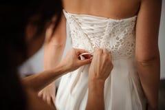 Demoiselle d'honneur faisant l'arc-noeud au dos de la robe de mariage de jeunes mariées Images stock