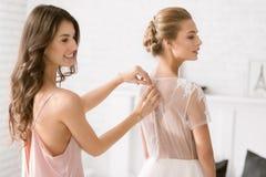 Demoiselle d'honneur gaie aidant la jeune mariée avec sa robe Images libres de droits