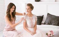 Demoiselle d'honneur heureuse aidant la jeune mariée avec sa robe Photos stock
