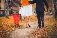 Demoiselle d'honneur, jeunes mariés marchant en parc Vue du dos Concept de mariage d'automne Photographie stock