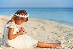 Demoiselle d'honneur s'asseyant sur la plage à la cérémonie de mariage Photos libres de droits