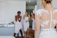 Demoiselles d'honneur étonnées regardant la jeune mariée dans la robe de mariage Images libres de droits