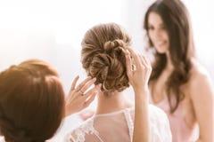 Demoiselles d'honneur agréables aidant la jeune mariée avec sa coiffure Photographie stock libre de droits