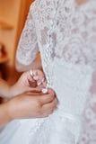 Demoiselles d'honneur aidant la jeune mariée à porter une robe de mariage Images libres de droits