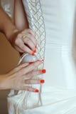 Demoiselles d'honneur aidant la jeune mariée à porter une robe de mariage Photographie stock