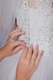 Demoiselles d'honneur aidant la jeune mariée Images stock