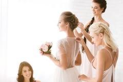 Demoiselles d'honneur avec plaisir aidant la jeune mariée à être prête Images stock