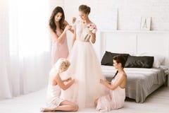 Demoiselles d'honneur avec plaisir aidant la jeune mariée à être prête Photographie stock