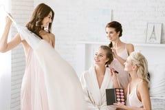 Demoiselles d'honneur avec plaisir aidant la jeune mariée à être prête Photo stock