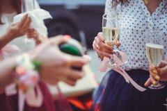 Demoiselles d'honneur avec un bouquet de mariage des fleurs à une cérémonie de mariage amies avec un boutonniere choyant le jour  Photo stock