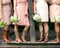 Demoiselles d'honneur dans des bottes de cowboy sur un porche rustique image libre de droits