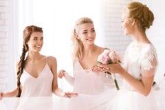 Demoiselles d'honneur de sourire tenant la robe de la jeune mariée Photos stock