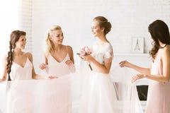 Demoiselles d'honneur de sourire tenant la robe de la jeune mariée Photo libre de droits
