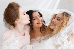 Demoiselles d'honneur et belle jeune mariée couvertes par le voile se tenant dans l'intérieur de chambre de grenier Portrait en g Photos stock