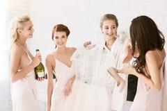 Demoiselles d'honneur gaies aidant la jeune mariée à être prête pour épouser Images stock