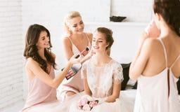 Demoiselles d'honneur gaies préparant la jeune jeune mariée à la cérémonie de mariage Photos libres de droits