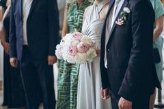 Demoiselles d'honneur magnifiques avec le bouquet de pivoine et garçons d'honneur élégants PO Photographie stock