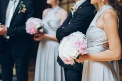 Demoiselles d'honneur magnifiques avec le bouquet de pivoine et garçons d'honneur élégants PO Images stock