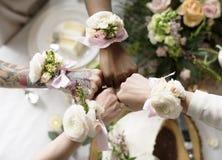 Demoiselles d'honneur montrant des bouquets de fleur sur leur poignet Photographie stock