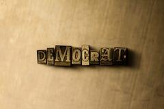 DEMOKRAT - närbild av det typsatta ordet för grungy tappning på metallbakgrunden Arkivbild