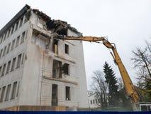 Demolera en gammal omodern byggnad med tungt maskineri royaltyfri fotografi