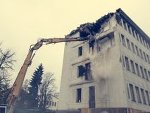 Demolera en gammal omodern byggnad med tungt maskineri arkivfoto
