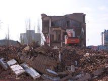 Demolição da construção velha em Novosibirsk entre as ruínas de uma máquina escavadora foto de stock royalty free