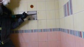 Demolição de telhas velhas com jackhammer Renovação de paredes velhas no banheiro ou na cozinha video estoque