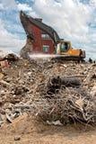 Demolierung eines Gebäudes durch einen Gleiskettenfahrzeugkran Stockfotos